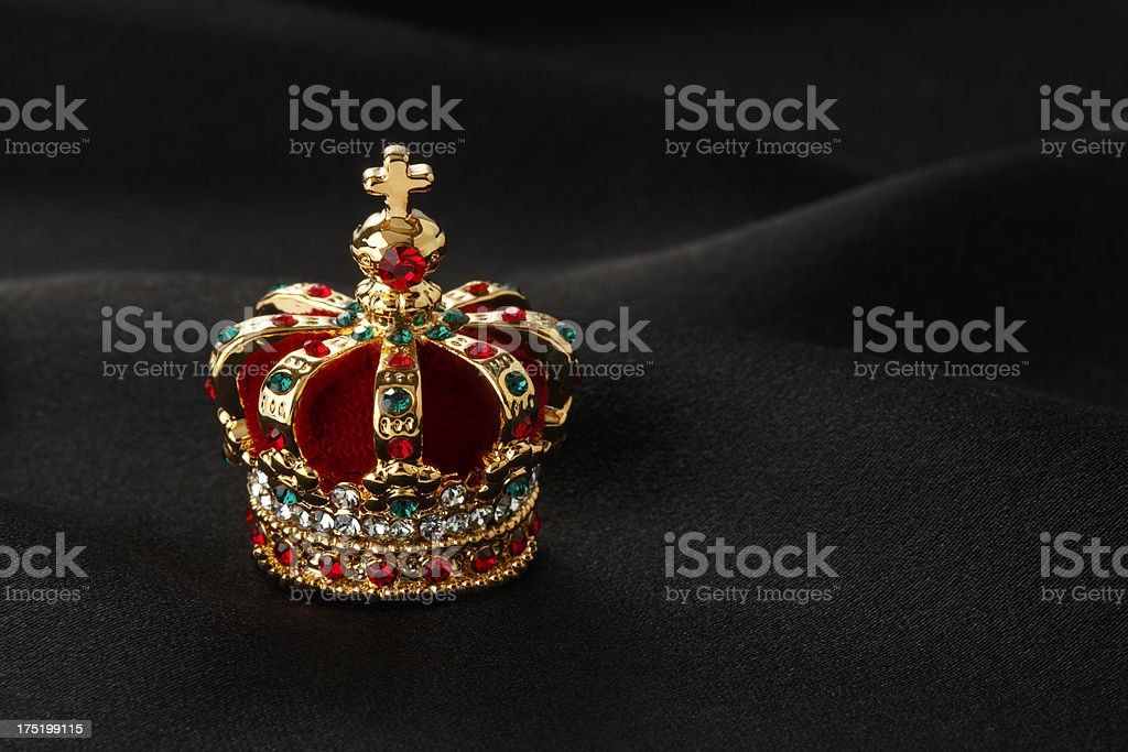 Gold crown with green and red jewels stock photo