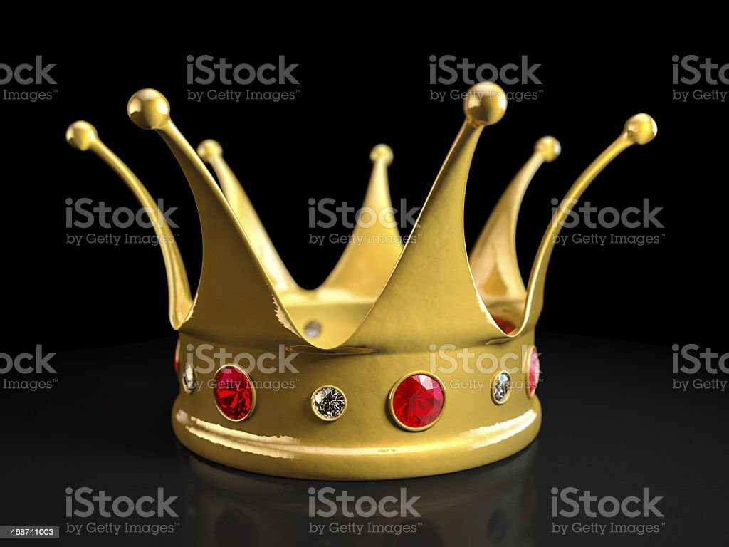 Gold crown with rubies and diamonds on black surface stock photo