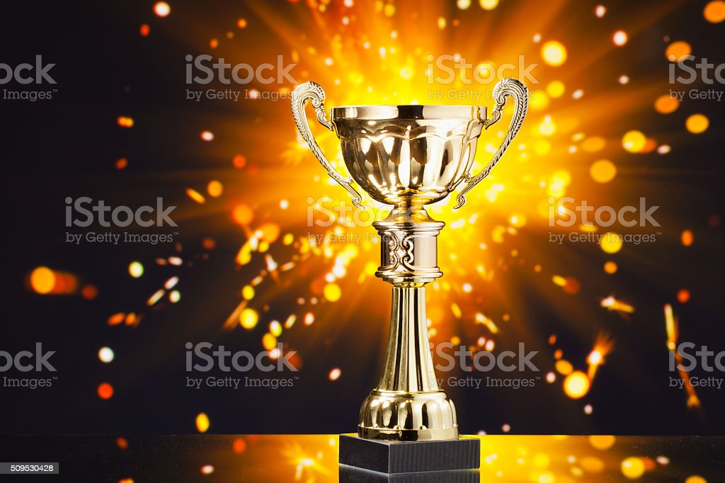 gold cup trophy against shiny sparks background stock photo