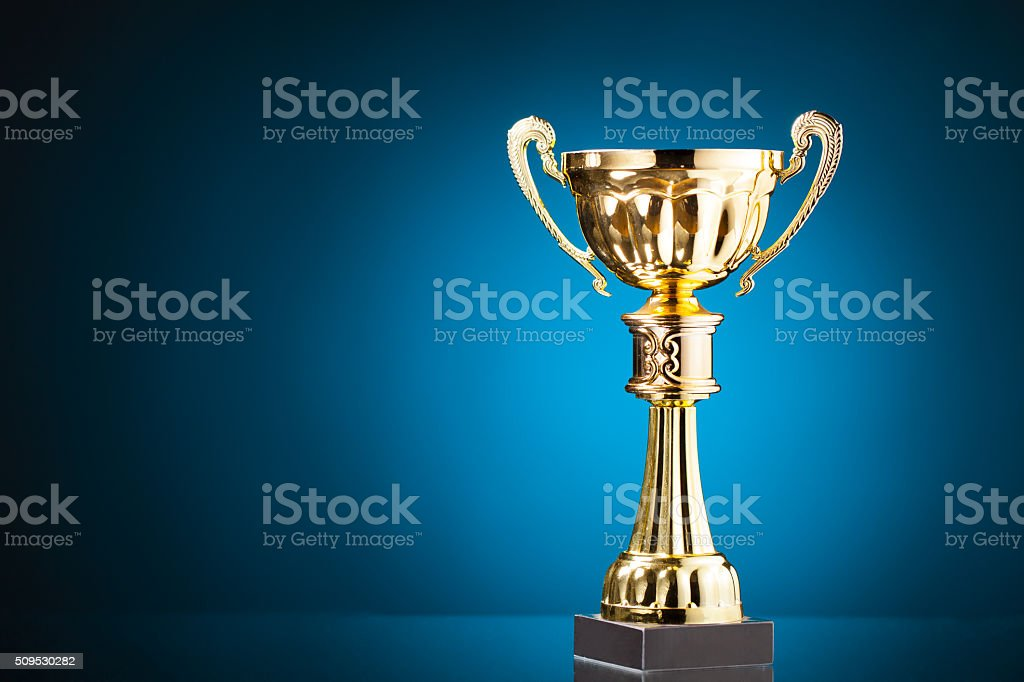 gold cup trophy on blue background stock photo
