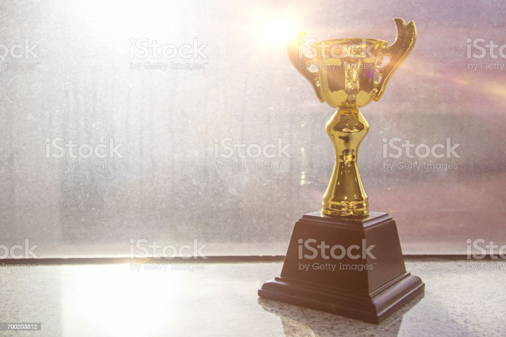 A gold cups as a reward for success or Award of achievement, near window reflecting on the beautiful sunshine. stock photo