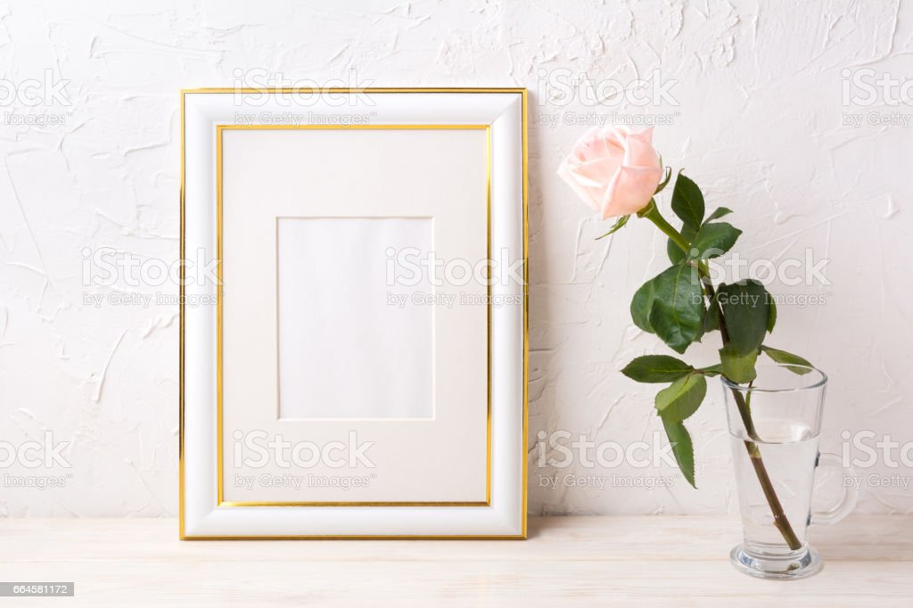 Gold decorated frame mockup with tender pink rose in glass. Empty...