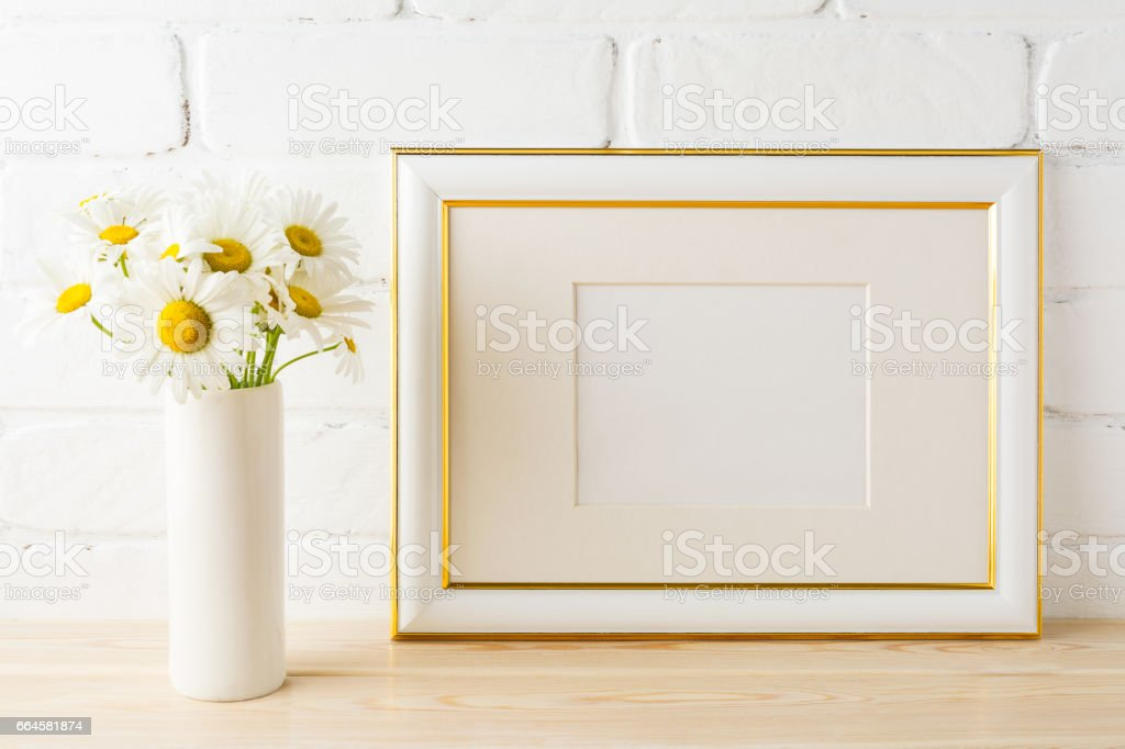 Gold decorated landscape frame mockup with daisy flower in vase stock photo