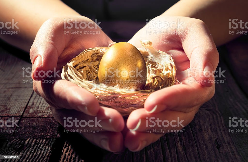 gold egg on hands - protection financial for future stock photo