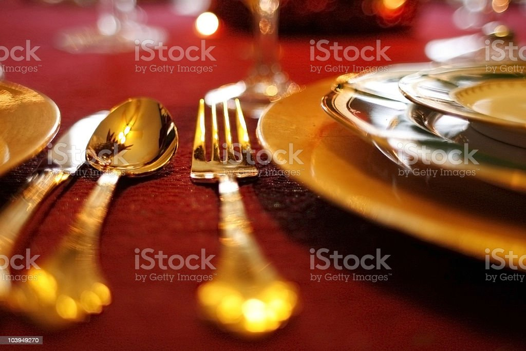 Gold Flatware Set on Red Tablecloth - Holiday Table Setting royalty-free stock photo