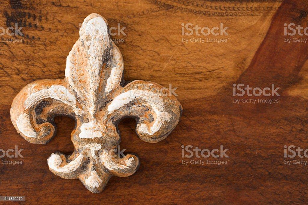 Gold fleur de lis on wooden table. stock photo