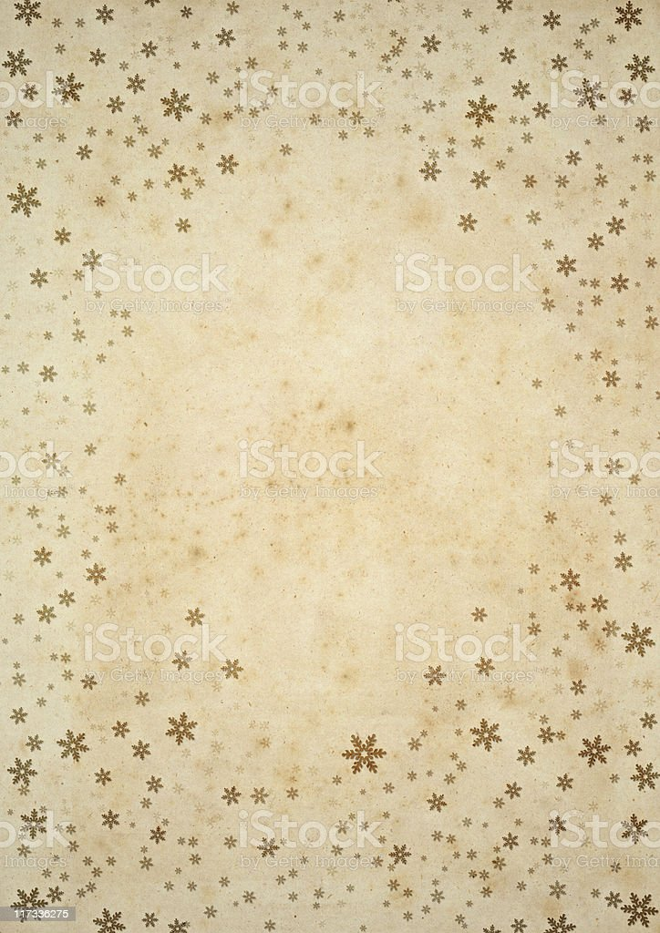 Gold foil snowflake on old paper winter background stock photo