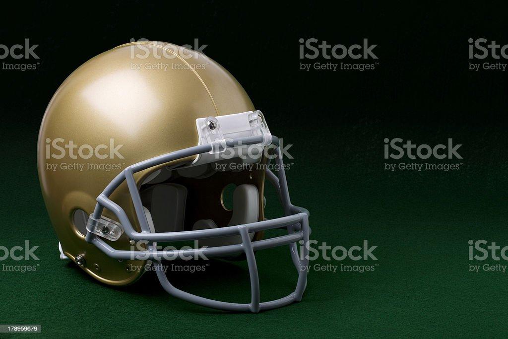Gold football helmet on green stock photo