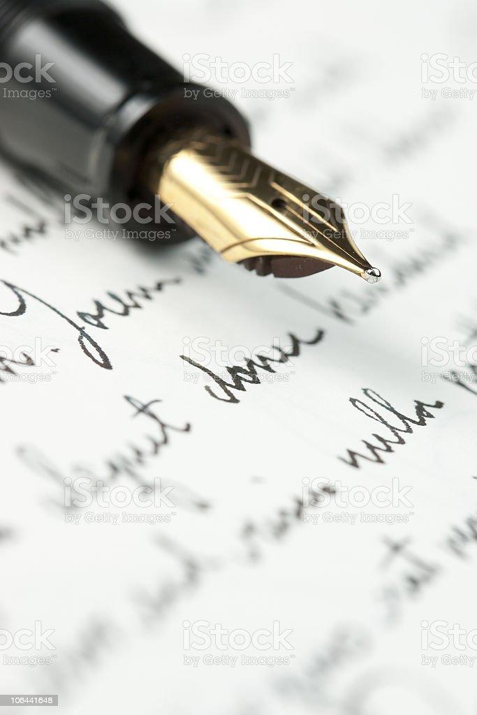 Gold fountain pen on hand written letter stock photo