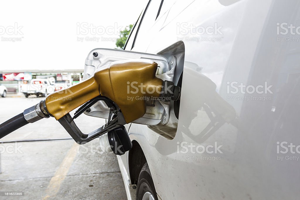 Gold fuel nozzle filling a white car stock photo