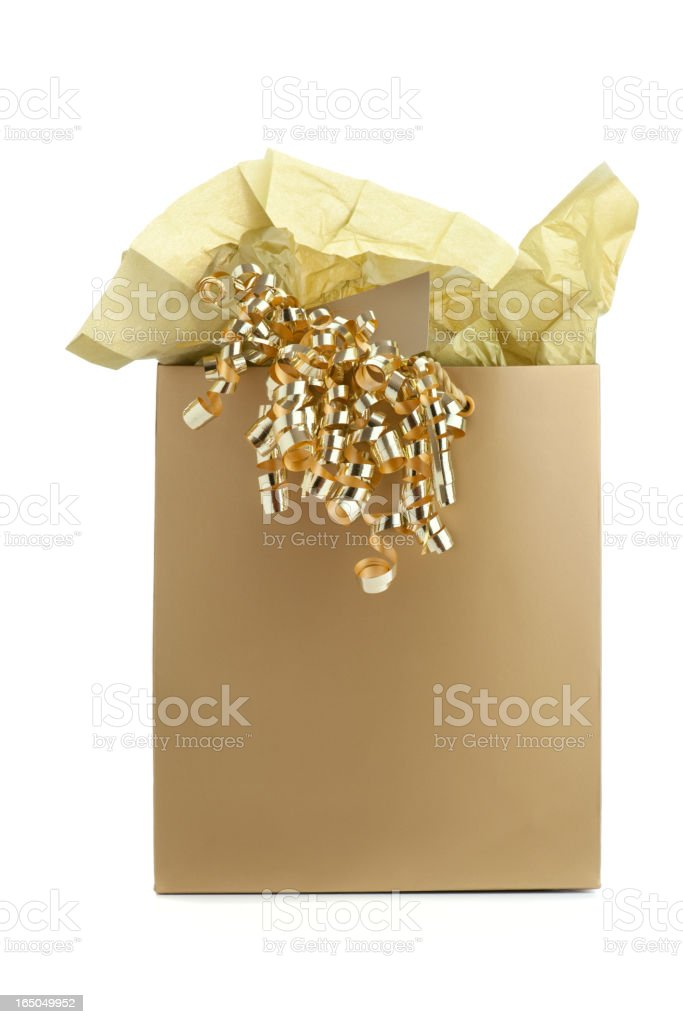 Gold gift bag with tissue paper and curly ribbon stock photo