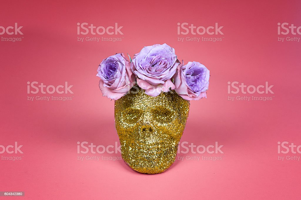 Gold Glitter Skull with Purple Rose Laurel on Pink Background stock photo