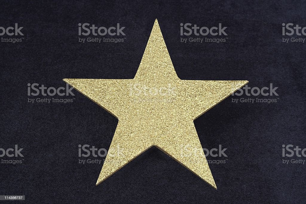 Gold Glitter Star On Dark Blue Velvet Bacground stock photo