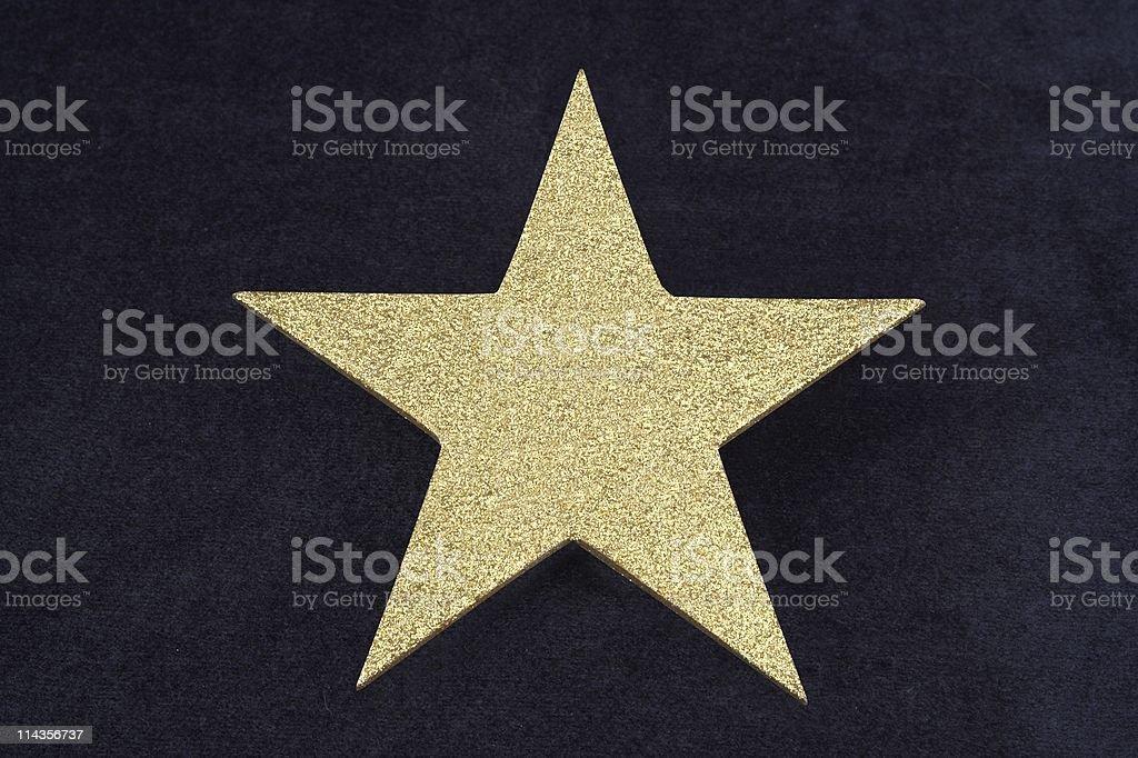 Gold Glitter Star On Dark Blue Velvet Bacground stock photo