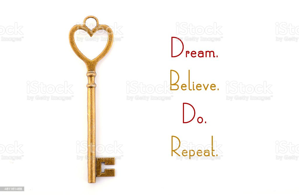 Gold heart shape key with inspirational phrase. stock photo