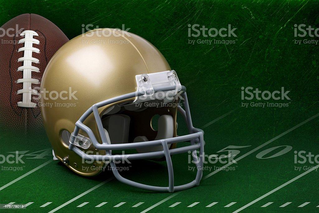 Gold helmet and football on dark green background stock photo