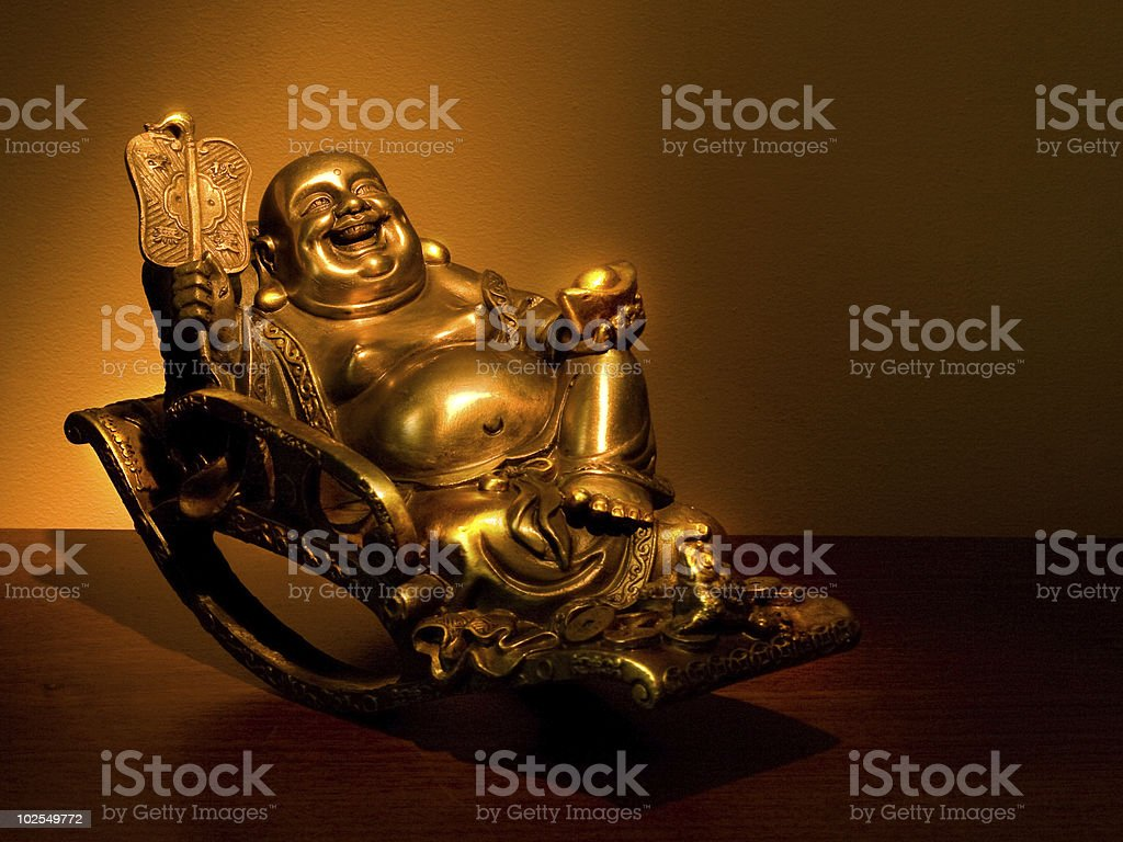 Gold Hotei seating in the rocking-chair royalty-free stock photo
