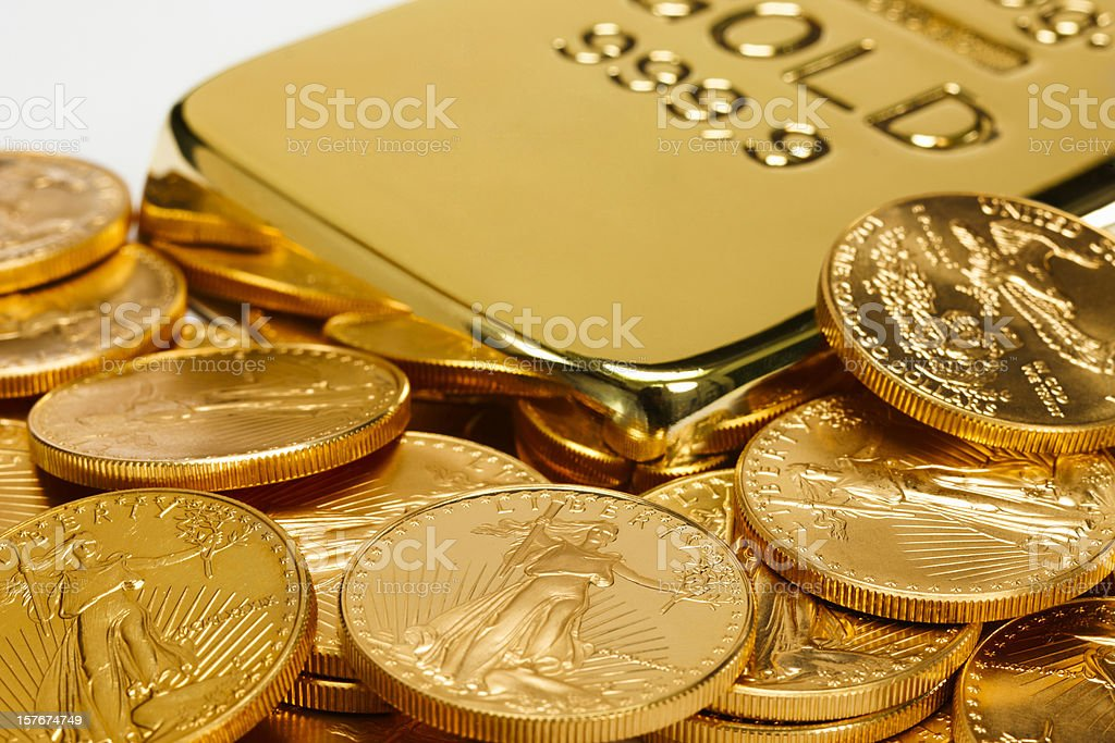 Gold ingot surrounded by golden coins stock photo