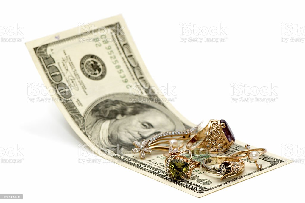 Gold jewelry lying on an American $100 bill royalty-free stock photo