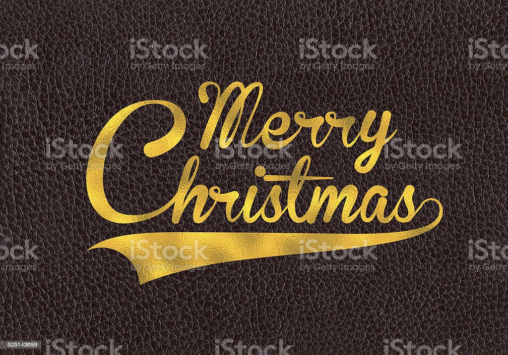 Gold leaf text Merry Christmas on brown leather royalty-free stock photo