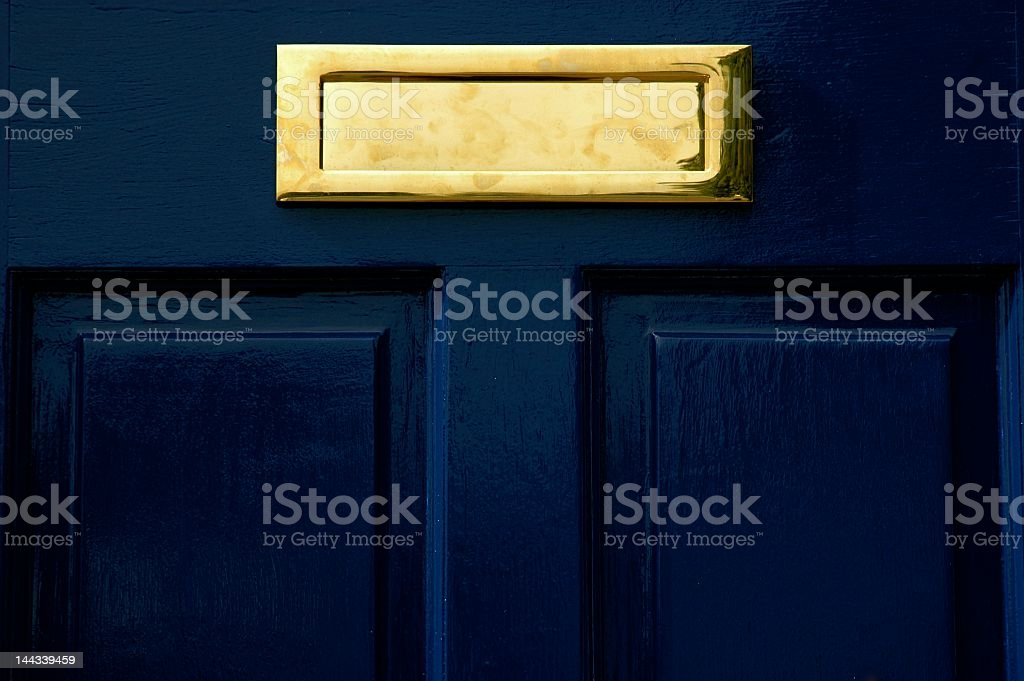 A gold letter box on a blue door stock photo