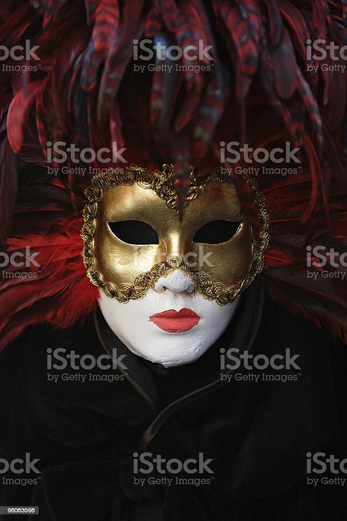 A gold mask with feathers being modeled by a whitened face  royalty-free stock photo