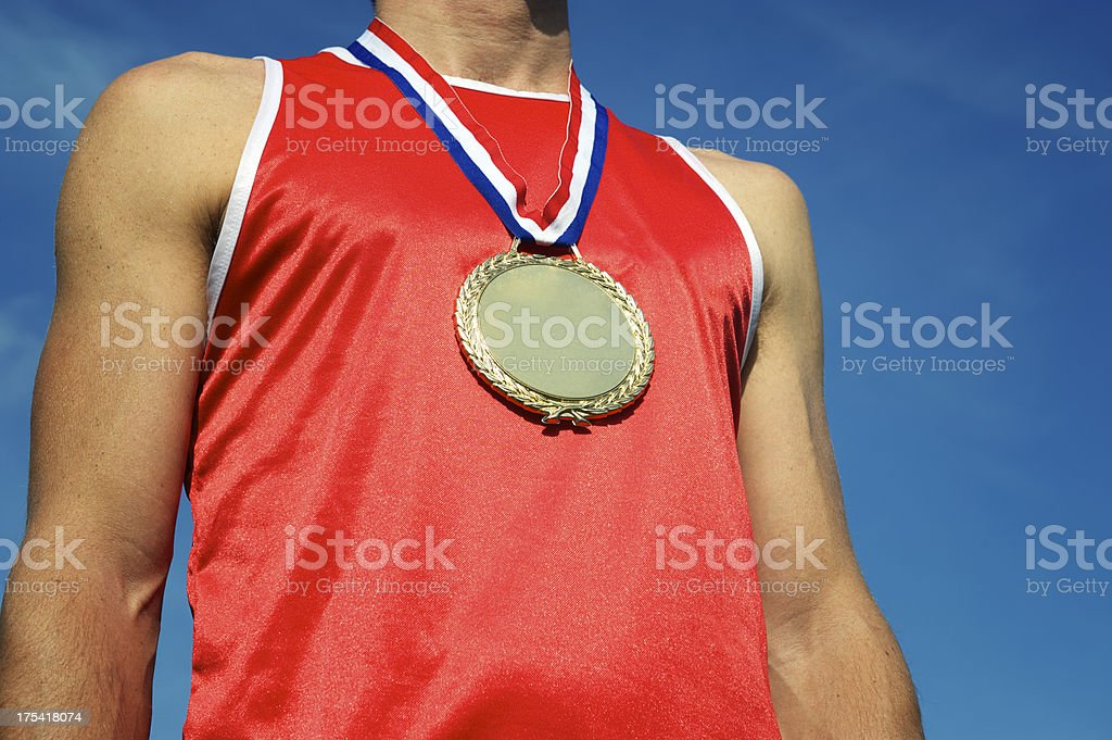 Gold Medal Athlete in Red Shirt Standing at Blue Sky royalty-free stock photo