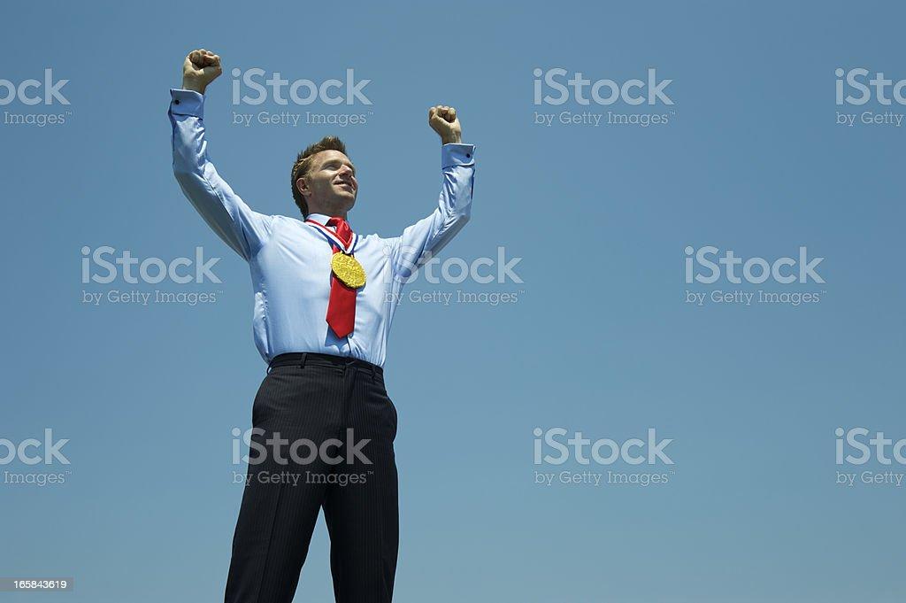 Gold Medal Businessman Celebrates Against Blue Sky royalty-free stock photo