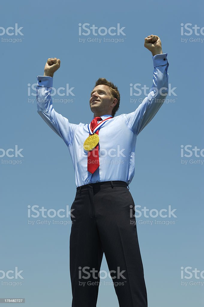Gold Medal Businessman Raises His Arms in Blue Sky royalty-free stock photo