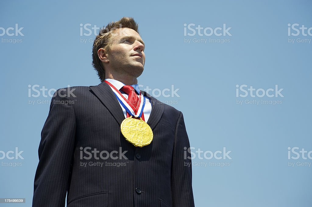 Gold Medal Businessman Stands in Blue Sky royalty-free stock photo