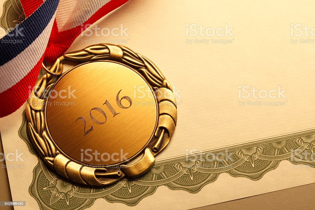 Gold Medal Inscribed With '2016' Resting On An Award Certificate stock photo