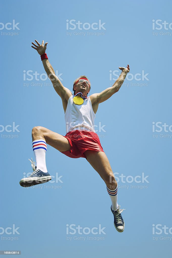 Gold Medal Nerd Athlete Jumps in Blue Sky royalty-free stock photo