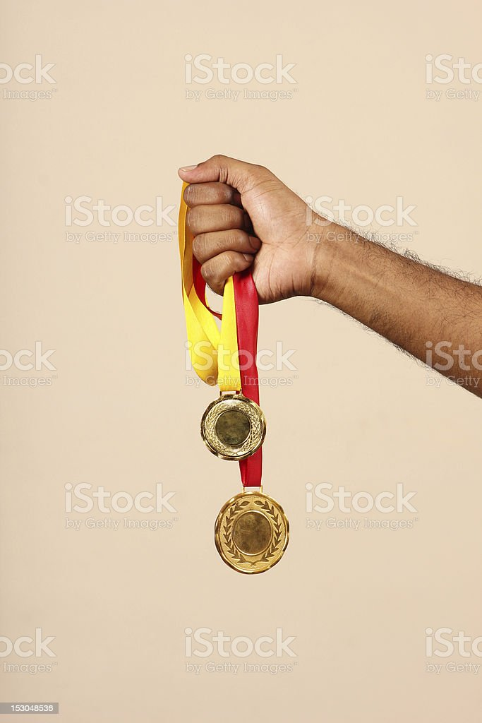 Gold medals in hand royalty-free stock photo