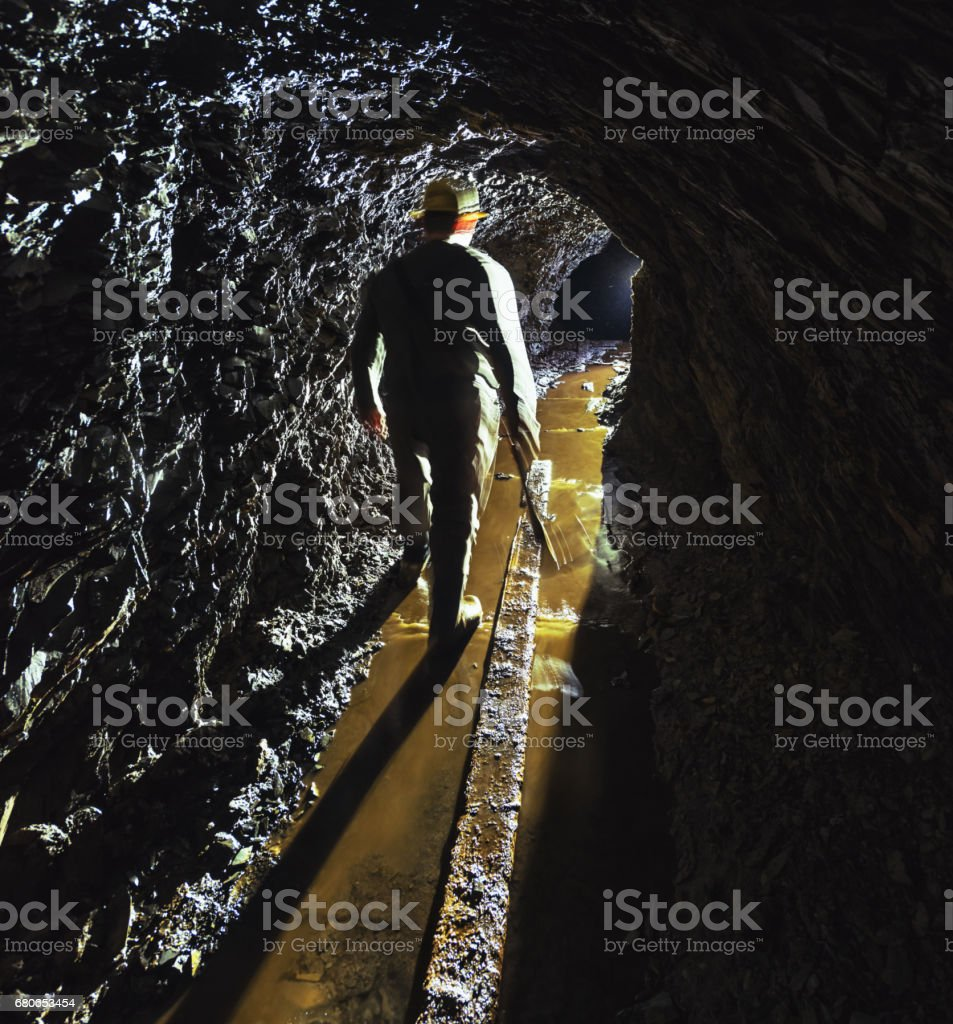 A gold miner is silhouetted in the narrow shaft of an abandoned gold...