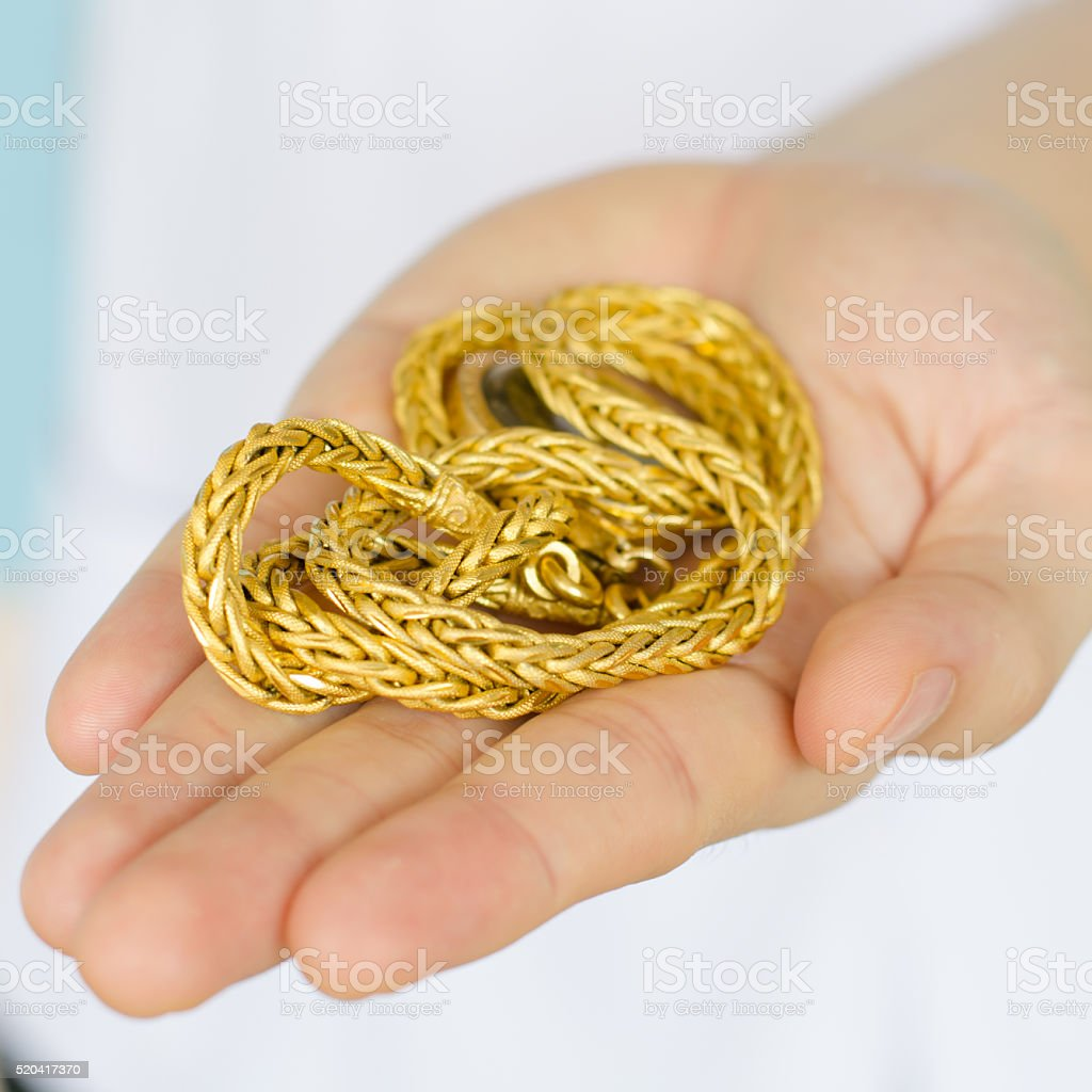 gold necklace in hand stock photo