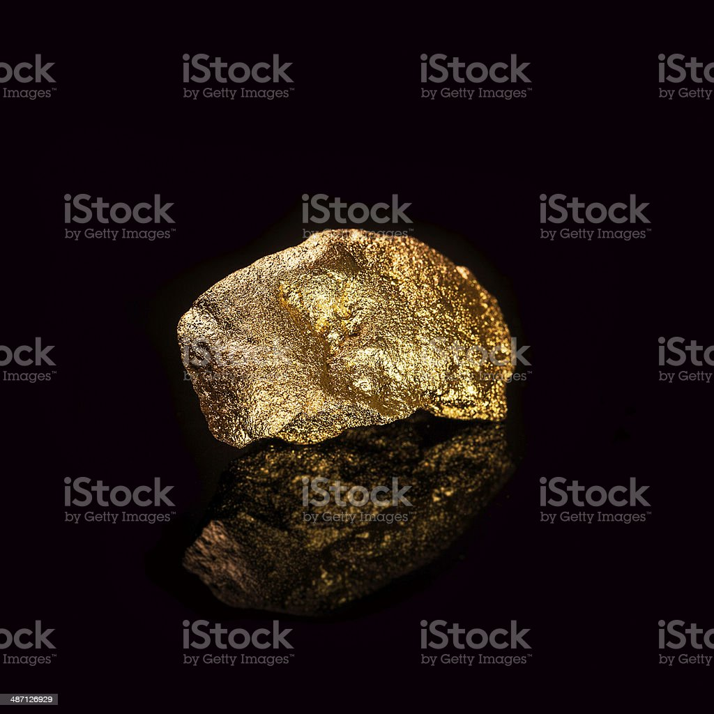 Gold nugget on black background. stock photo