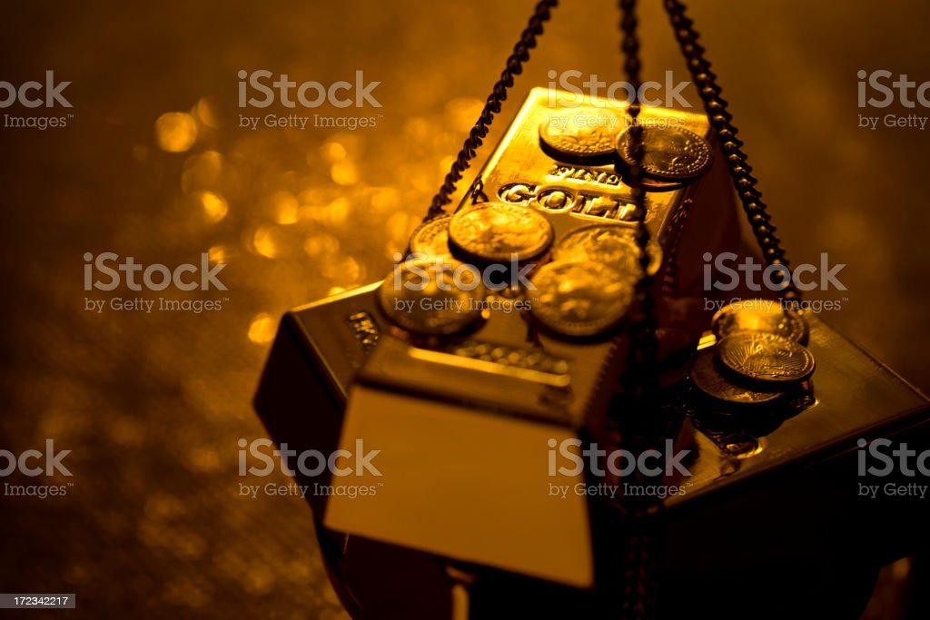 Gold on a weight scale royalty-free stock photo