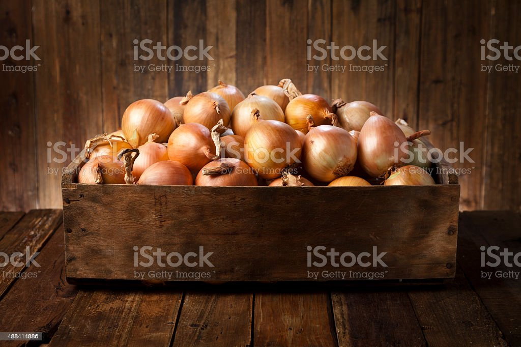 Gold onions in a wooden crate on rustic wood table stock photo