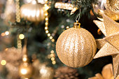 Gold ornaments and decorations on Christmas tree.