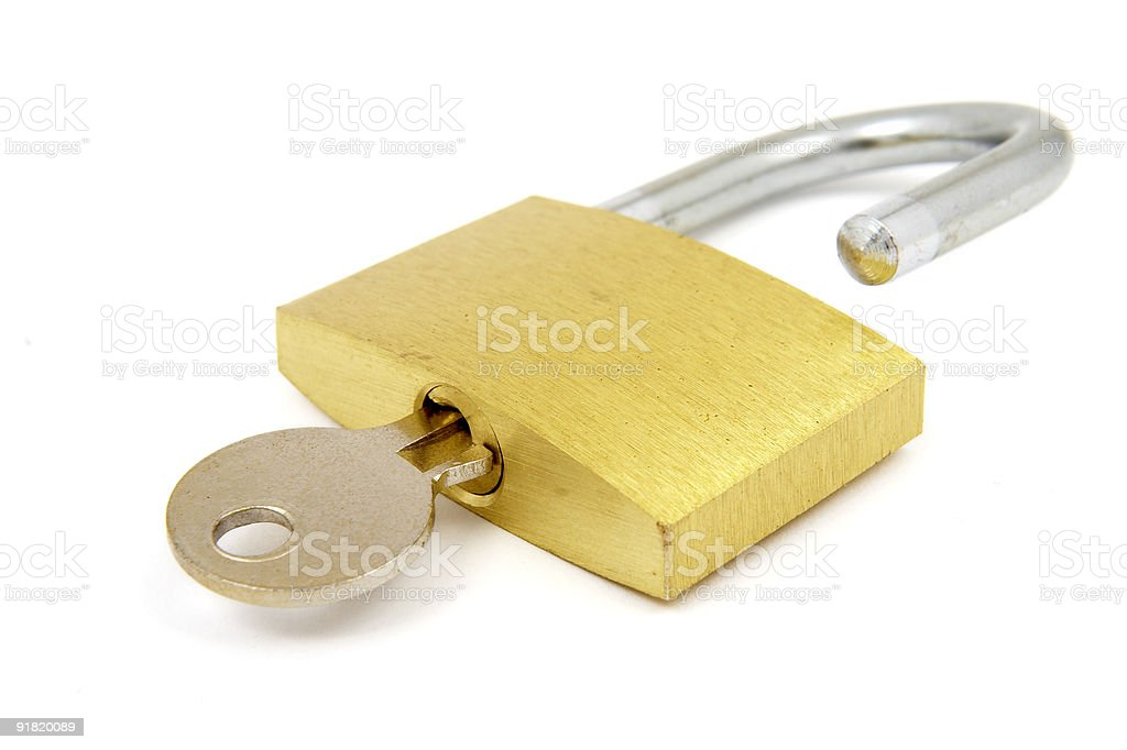 Gold padlock with key in it on a white backdrop stock photo