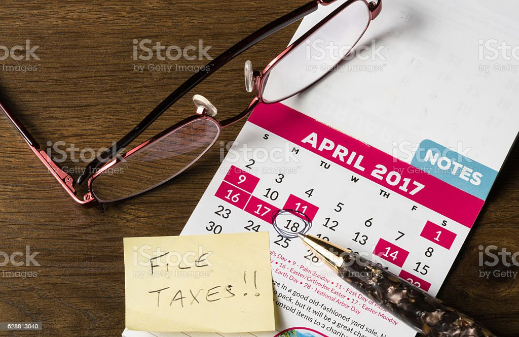 Gold pen laying on calendar for tax day stock photo