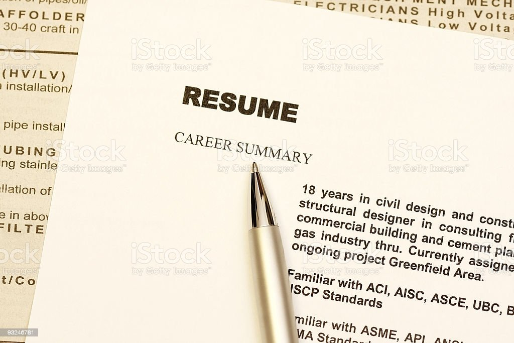 Gold pen resting on top of a printed resume royalty-free stock photo
