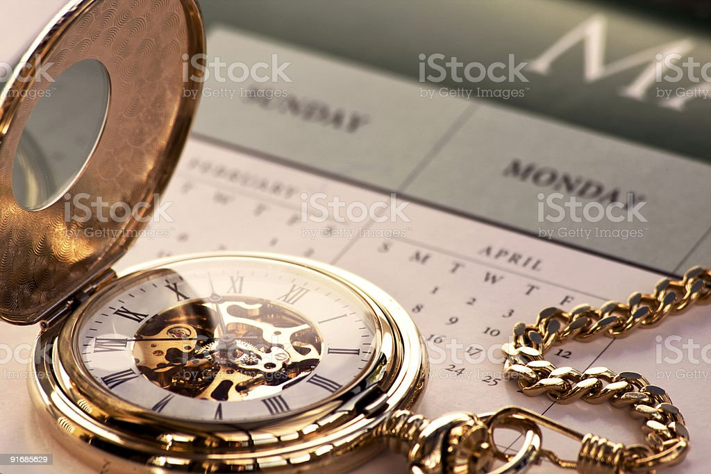 Gold pocket watch and calendar royalty-free stock photo