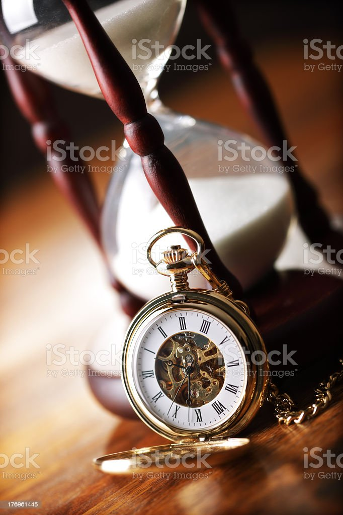 Gold pocket watch laying against hourglass on wooden table stock photo