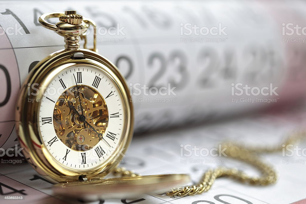 Gold pocket watch leaning against a calendar stock photo