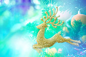 Gold Reindeer on Christmas Tree Decoration and blurry background