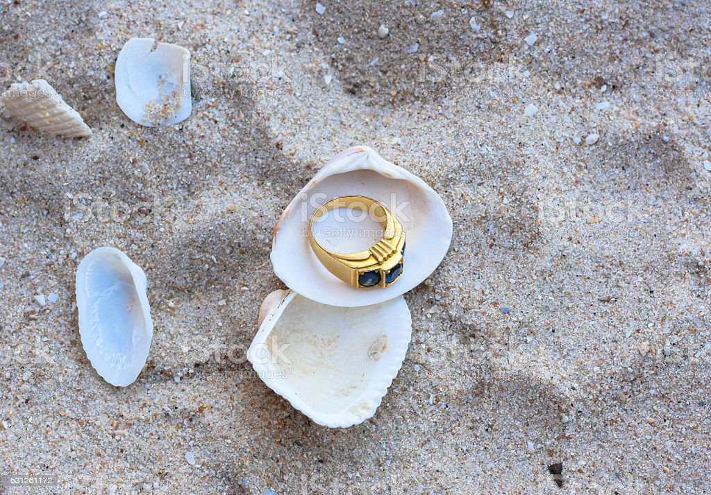 Gold Ring on shell and sand stock photo
