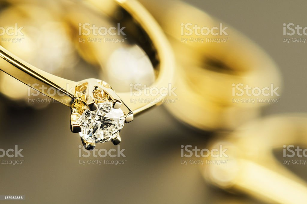 Gold ring with big diamond against jewelry background stock photo