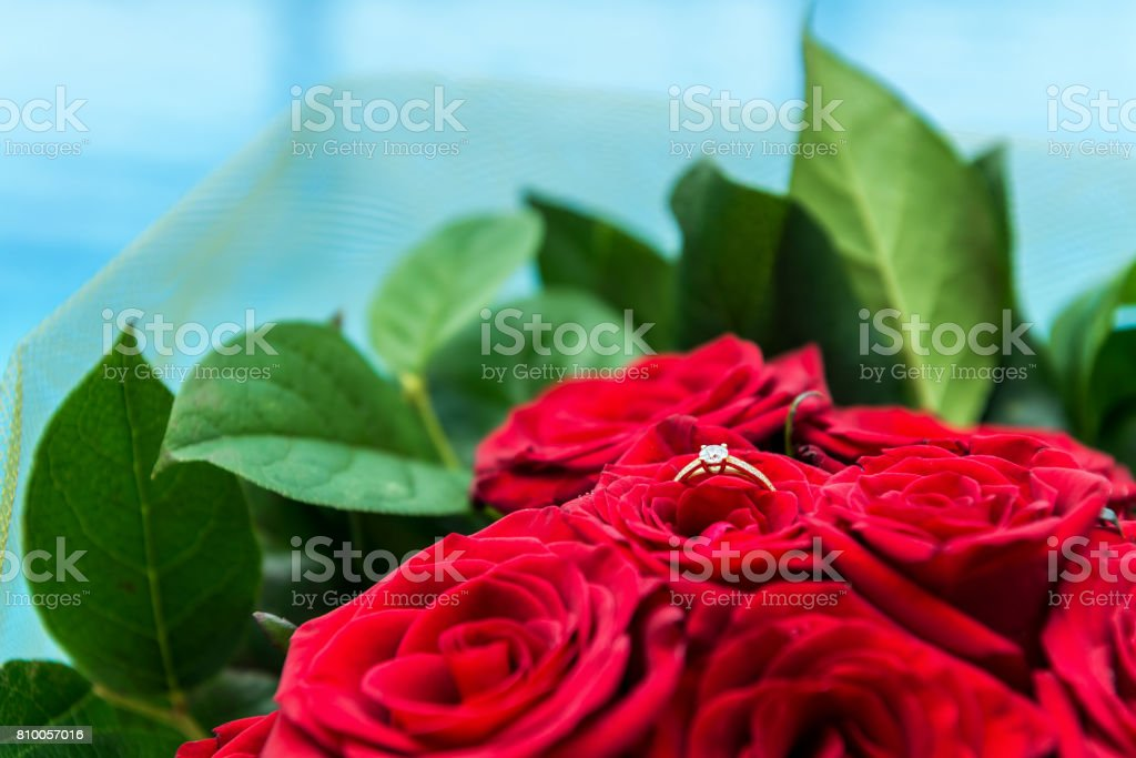 Gold ring with diamond in bouquet of roses stock photo