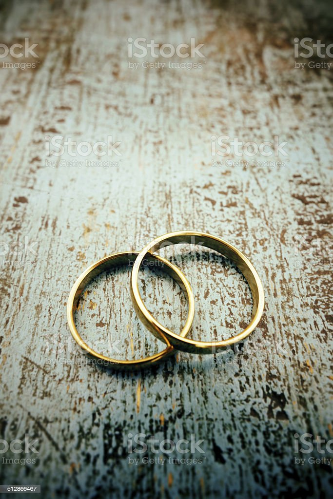 Gold rings on blue wood stock photo